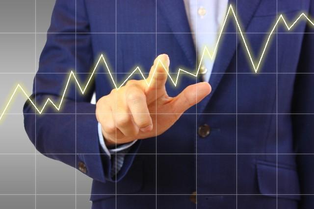 上昇するグラフをなぞるビジネスマン