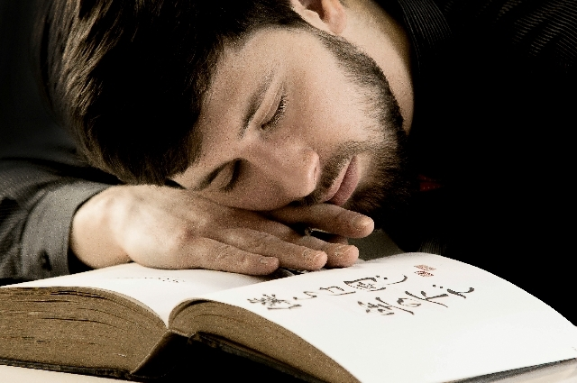 本を読みながら眠る男性