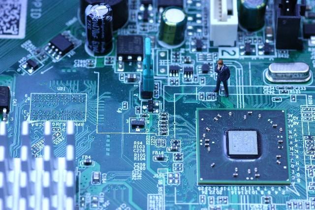 電子基板の上のミニチュアサラリーマン